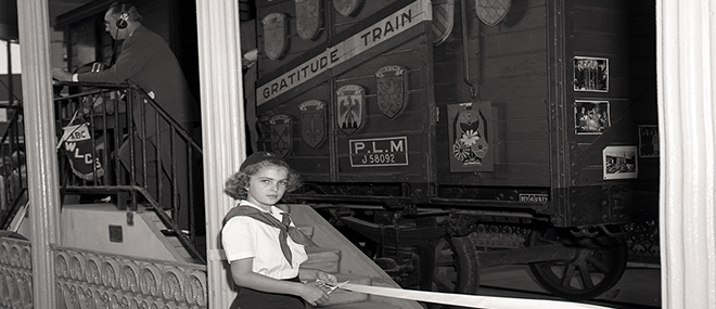 A girl poses by the Merci Train, a gift to Louisiana from France after World War II, at Louisiana's Old State Capitol. John Gasquet, photographer